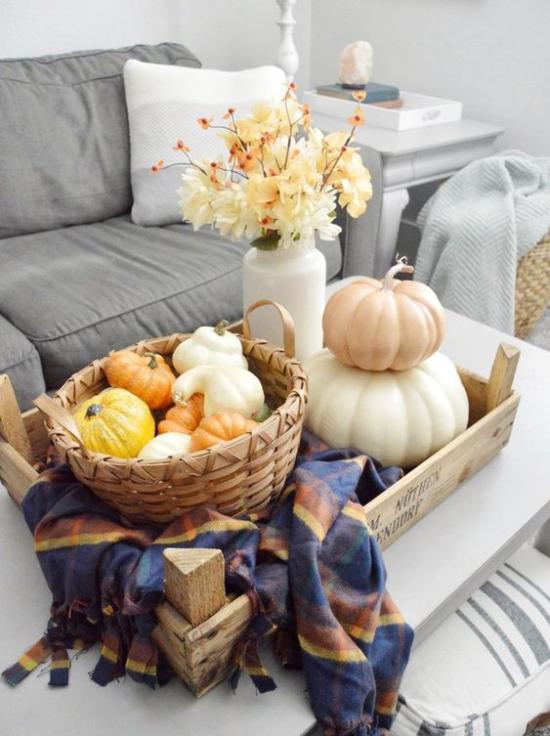 Herbstdeko auf dem Kaffeetisch zwei Kürbisse auf dem Tisch weiße Vase mit orangenfarbenen Blumen Flechtkorb mit Zierkürbissen karierte Tischdecke