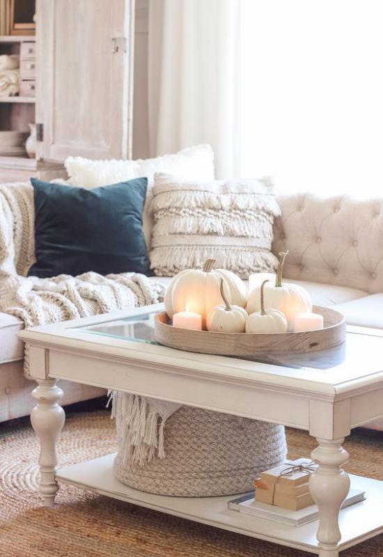Herbstdeko auf dem Kaffeetischgemütliches Wohnzimmer in Weiß gestaltet weißes Ecksofa weißer Tisch weiße Kürbisse Kerzen