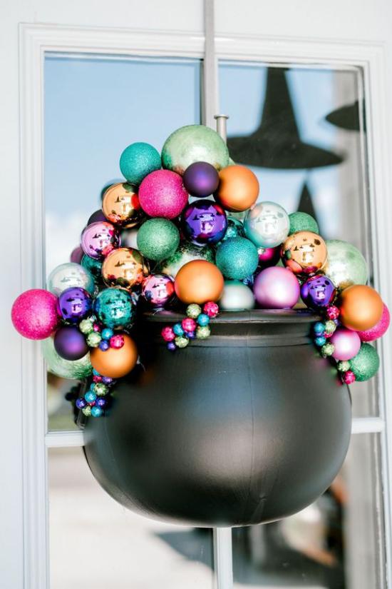 Hexenkessel Blickfang in der Halloween Deko schwarzer Kessel voll mit bunten glitzernden Kugeln