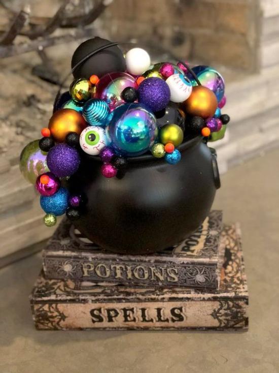 Hexenkessel Halloween Deko drinnen alte Bücher schwarzer Kessel voll mit glitzernden Kugeln