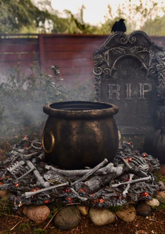 Hexenkessel draußen Grabstein Holzfeuer gruselige Umgebung viel Mysteriöses