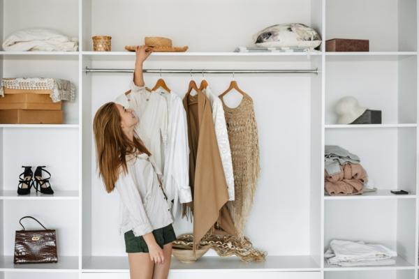 Beautiful caucasian nice girl choosing clothes by wardrobe at home