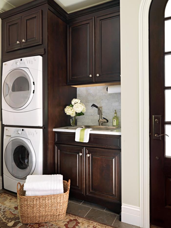 Waschküche sehr stilvoll gestaltet dunkelbraune Schränke weiße Geräte Waschmaschine Trockner im visuellen Farbkontrast