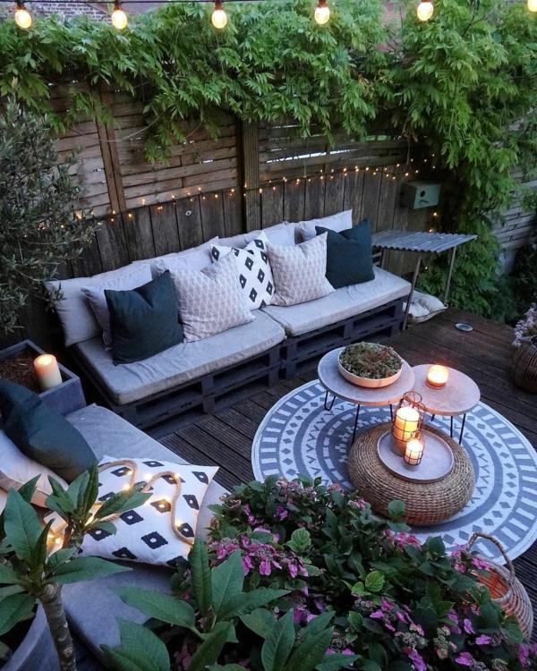 gartengestaltung beispiele gemütlicher hinterhof kerzen lichterketten dekokissen