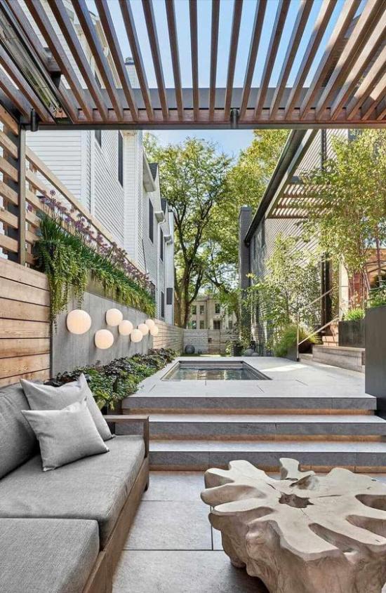 minimalistische Terrassengestaltung Überdach Sitzbank graue Sitzkissen Treppen Pool grüne Pflanzen runde Lampen