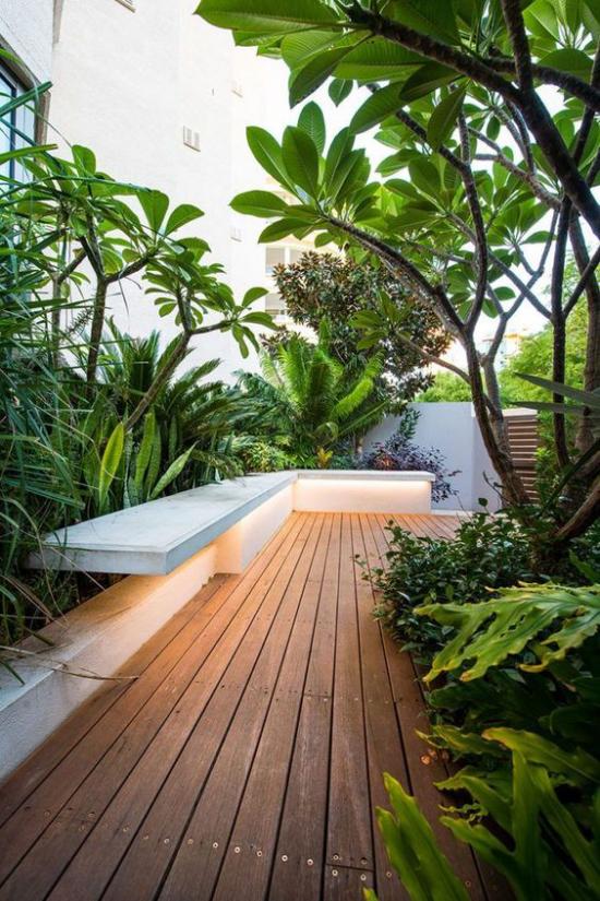 minimalistische Terrassengestaltung üppiges sattes Grün umrahmt die Veranda im minimalistischen Stil