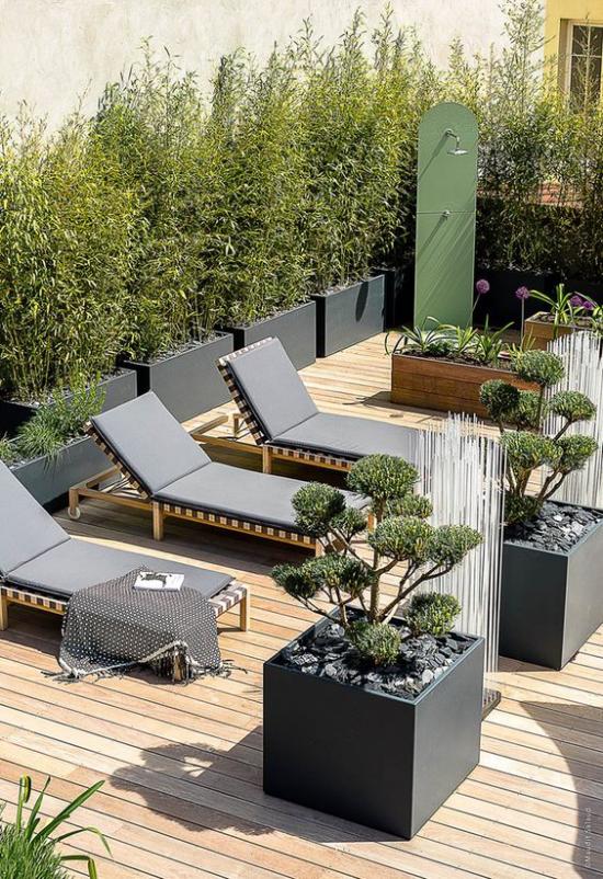 minimalistische Terrassengestaltung Dachterrasse Ruheort geflochtene Liegestühle große Pflanzkübel viel Grün