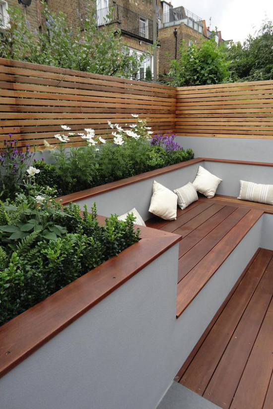 minimalistische Terrassengestaltung Holzboden Holzbank blühende Pflanzen ringsum