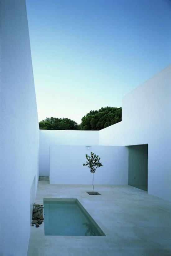 minimalistische Terrassengestaltung Minimalismus pur weiße Wände Sichtschutz Betonboden kleiner Pool ein Baum daneben