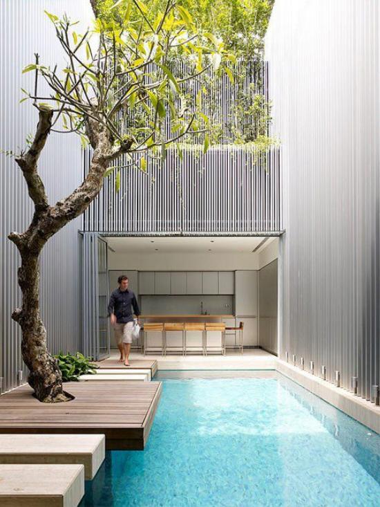 minimalistische Terrassengestaltung Pool junger Mann daneben kleine Terrasse zwischen Häuser im minimalistischen Stil keine Möbel nichts Überflüssiges