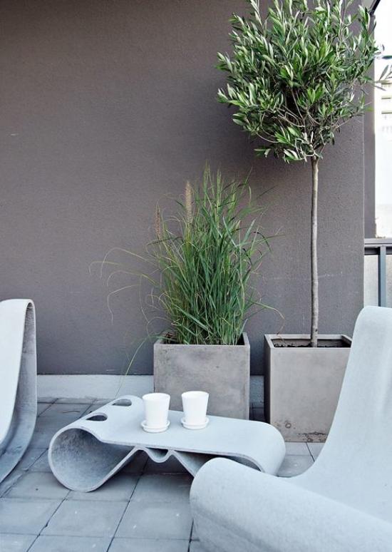 minimalistische Terrassengestaltung ausgefallene minimalistische Möbel zwei Betonkübel grüne Pflanzen Grau dominiert