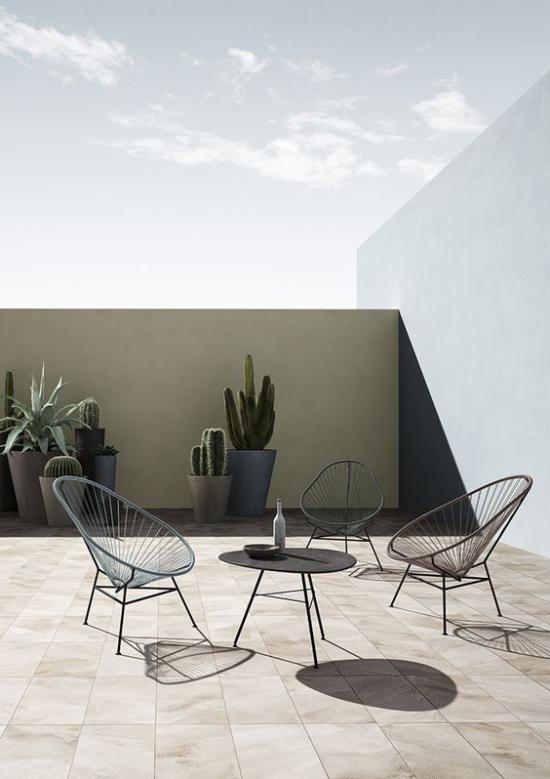 minimalistische Terrassengestaltung einfaches Gestaltungskonzept runder Tisch Stühle aus Metall Betonkübel mit Sukkulenten