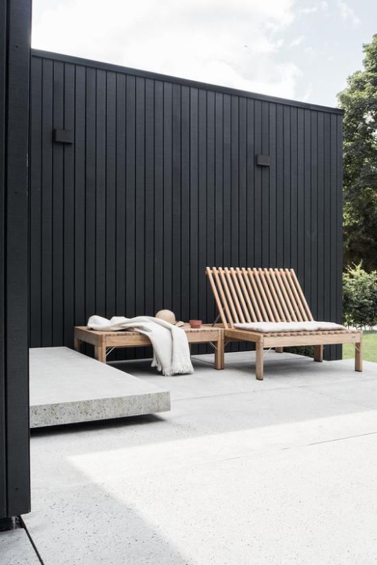 minimalistische Terrassengestaltung einfaches Gestaltungskonzept schwarze Wand Betonboden Holzbank nichts Überflüssiges