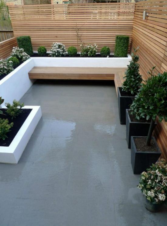 minimalistische Terrassengestaltung kleine Terrasse in der Stadt Betonboden klare Linien Kübel grüne Pflanzen