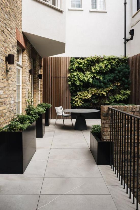 minimalistische Terrassengestaltung kleine Terrasse in der Stadt zwischen Häusern minimalistisch gestaltet großformatige Bodenfliesen hohe Pflanzkübel runder Tisch Metallstuhl