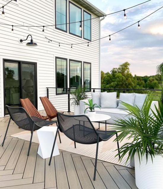 minimalistische Terrassengestaltung reduzierte Terrasseneinrichtung runder Tisch Metallstühle hellgraue Outdoor-Couch
