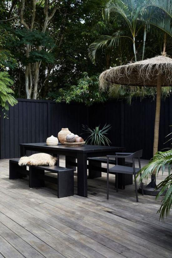 minimalistische Terrassengestaltung schwarze Möbel Wände Holzboden helle Deko Artikel