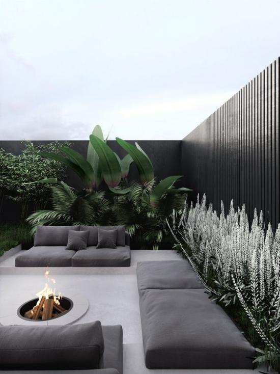 minimalistische Terrassengestaltung verschiedene Graunuancen schwarze Wand Sitzmöbel Feuerstelle viele grüne Pflanzen ringsum