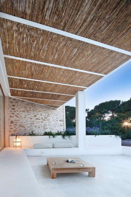 minimalistische Terrassengestaltung weite Sitzecke niedrige gepolsterte Sitzmöbel in Weiß niedriger Holztisch Überdach Lampe Outdoor-Beleuchtung