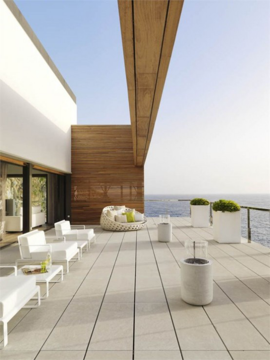 minimalistische Terrassengestaltung weite Terrasse einfaches Gestaltungskonzept helle Farben weiße Pflanzkübel herrliche Ozeansicht