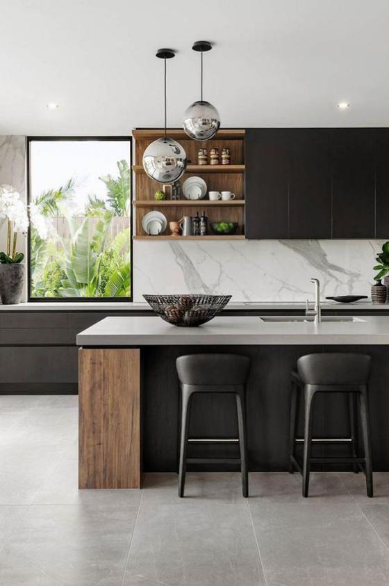 moderne Küche Marmor an der Küchenrückwand schwarze Schränke helles Holz graue Bodenplatten