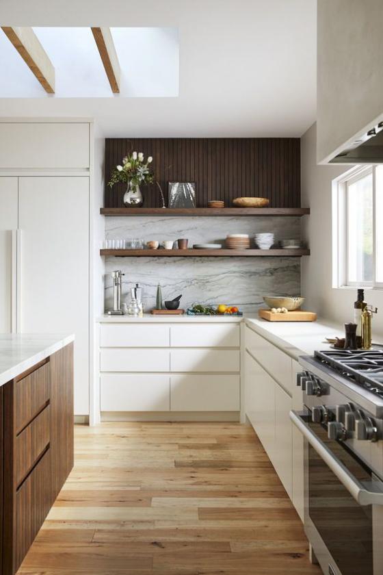 moderne Küche elegantes L-förmiges Küchendesign Fenster weißer Marmor weiße Schränke dunkles Holz