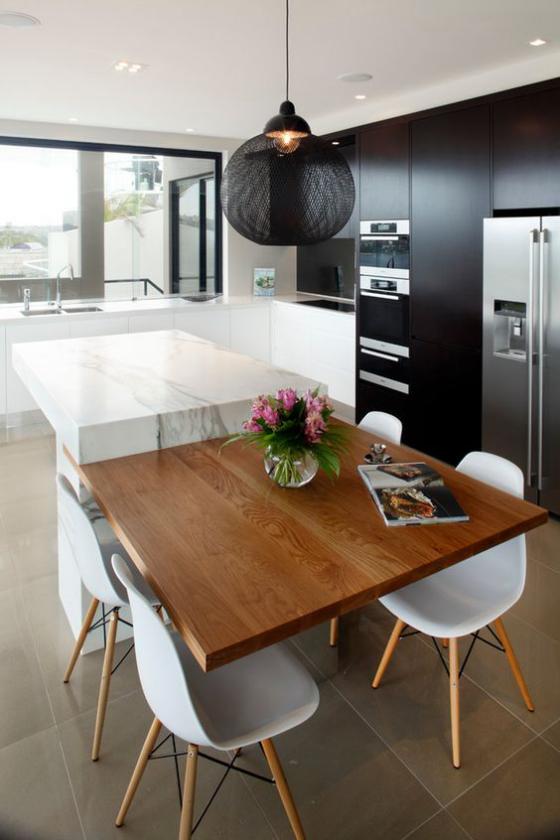 moderne Küche extravagantes Küchendesign schwarze grifflose schränke eingebaute Geräte weiße Kücheninsel Holzplatte weiße Stühle schwarze Hängelampe
