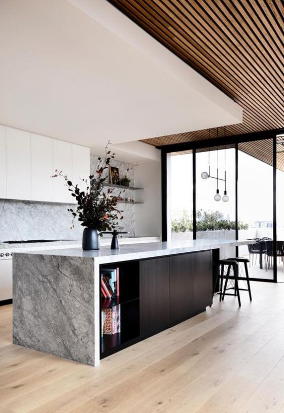 moderne Küche grauer Marmor schwarzes Holz Kücheninsel zum Blickfang machen schwarze Vase darauf schwarze Blumen