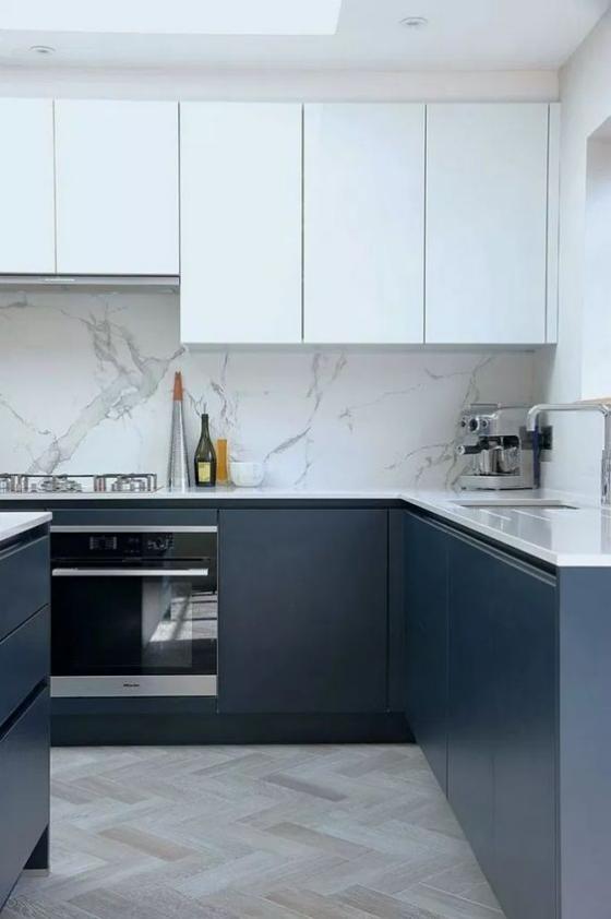 moderne Küche grifflose Schränke weiße Oberschränke marineblaue Unterschränke Küchenrückwand aus hellgrauem Marmor