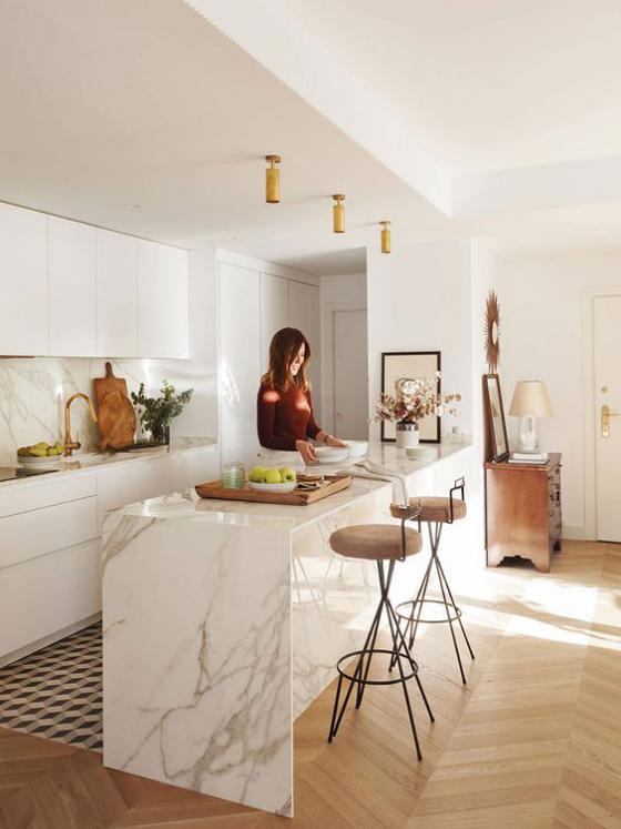 moderne Küche sehr elegantes Design große Kücheninsel aus weißem Marmor junge Frau beim Speisenzubereitung
