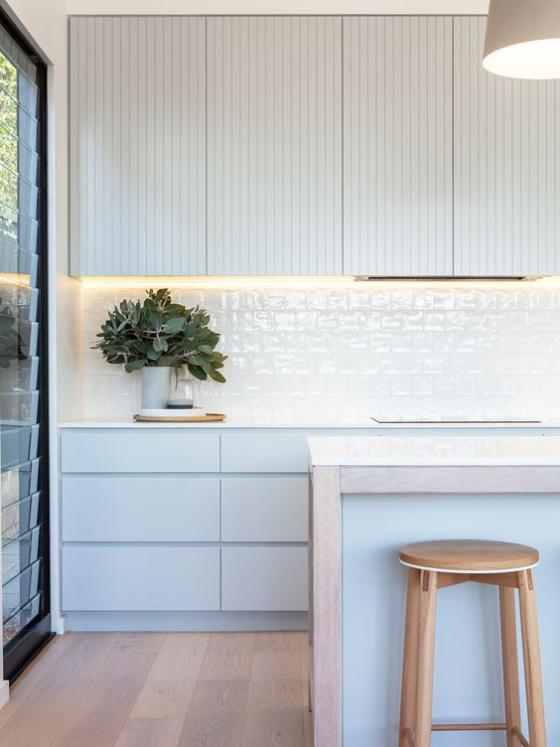 moderne Küche weiße Fliesen nicht altmodisch leicht glänzende hellblaue Schubladen Hocker aus hellem Holz