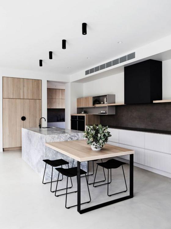 moderne Küche weiße Kücheninsel aus Marmor gepaart mit hellem Holz Tisch Schränke schwarze Hocker schwarze Deckenstrahler