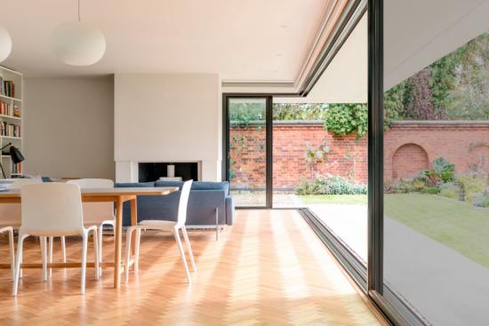 Faltfenster moderne Fensterkonstruktion elegant eingerichtetes Wohnzimmer viel Tageslicht Sonnenstrahlen angenehme Raumatmosphäre