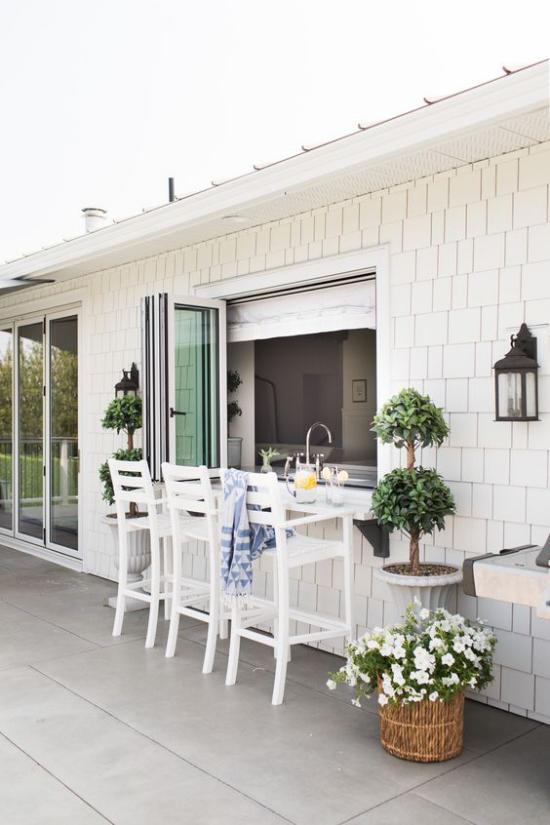 Faltfenster moderne Fensterkonstruktion elegante Sitzecke Getränke trinken an Schnittstelle zwischen drinnen und draußen grüne Pflanzen Korb mit weißen Blumen