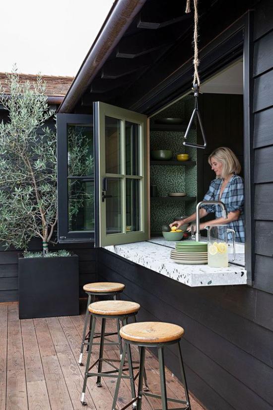 Faltfenster moderne Fensterkonstruktion geöffnet direkten Kontakt leichter Übergang zum Outdoor-Bereich Frau beim Kochen in der Küche