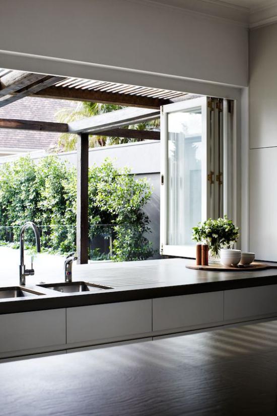 Faltfenster moderne Fensterkonstruktion von der Küche aus das Grün im Garten bewundern