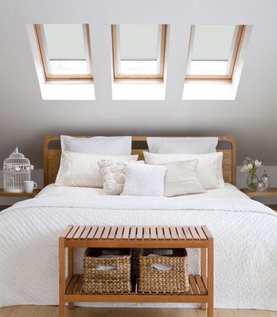 Moderne Dachfenster im Schlafzimmer über dem Schlafbett romantische Raumgestaltung weiter Bett weiße Bettdecke Kissen helles Holz