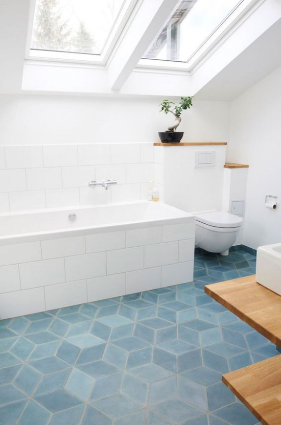 Moderne Dachfenster schicke Badgestaltung hellblaue Bodenfliesen weiße Badewanne viel Tageslicht