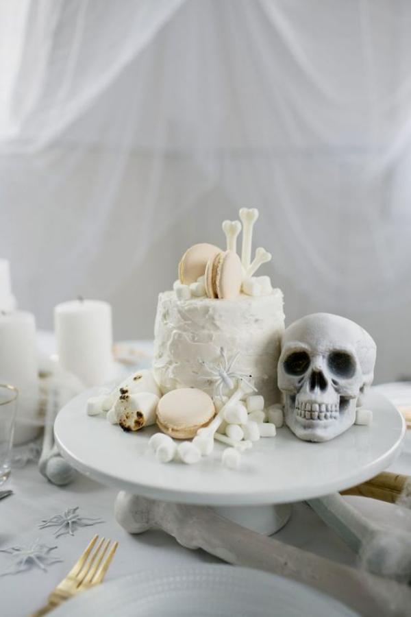 Weiße Halloween Deko Ideen auf dem Esstisch Etagere Totenkopf weiße Torte Knochen