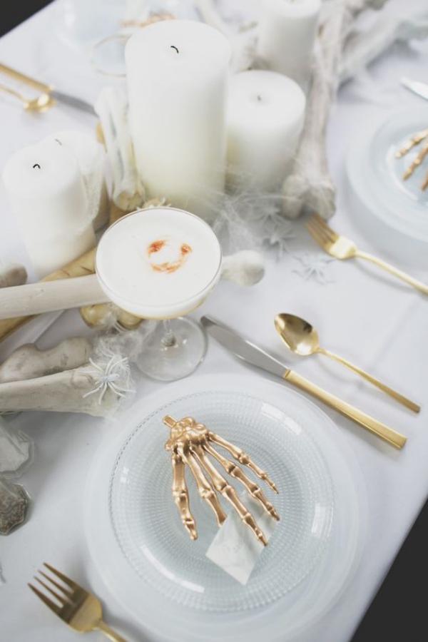 Weiße Halloween Deko Ideen festlich gedeckter Tisch weißer Schmuck Hand in goldgelb auf einem weißen Teller weiße Kerzen