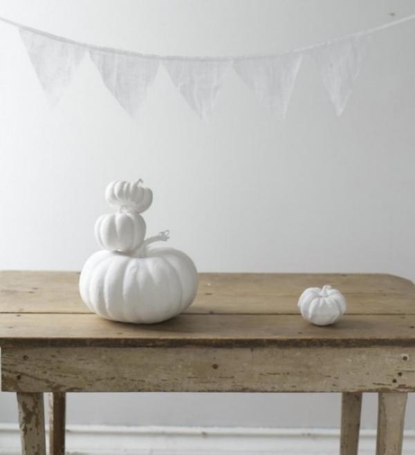 Weiße Halloween Deko Ideen minimalistischer gruseliger Raumschmuck weiße Kürbisse Girlande kleine weiße Dreiecke
