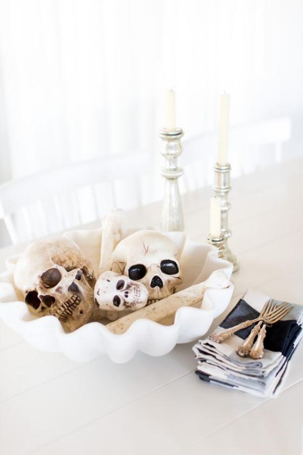Weiße Halloween Deko Ideen spezielle weiße Deko für Halloween Buffet große weiße Schale mit Totenköpfe gefüllt weiße Kerzen daneben schrecklich wirken