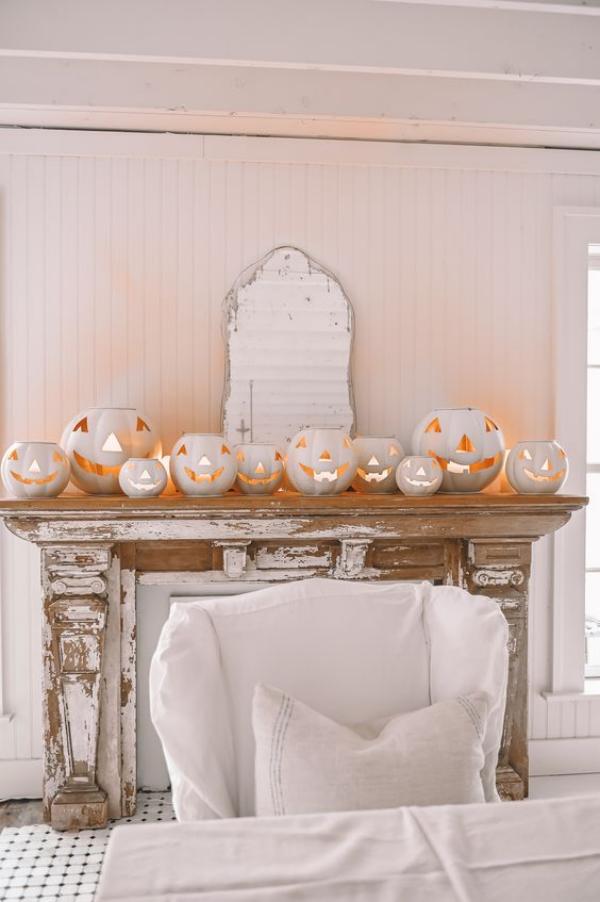 Weiße Halloween Deko Ideen weiße Kürbisse auf dem Kaminsims mit Kerzen oder Lichter drin alter Spiegel ringsherum alles Weiß
