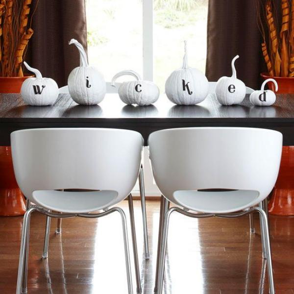 Weiße Halloween Deko Ideen weiße Kürbisse auf einem schwarzen Esstisch geschnitzt beschrieben Angst verbreiten