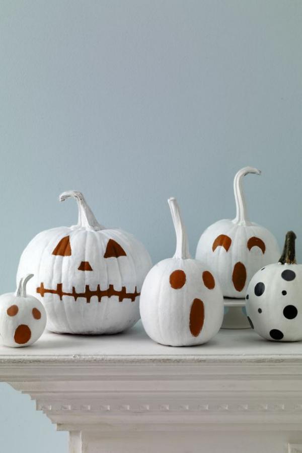 Weiße Halloween Deko Ideen weiße Kürbisse mir schreckenerregenden Fratzen auf einem Tisch arrangiert