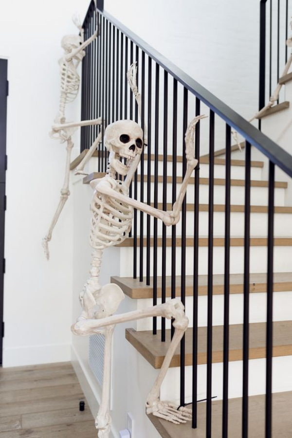 Weiße Halloween Deko Ideen zwei weiße Skelette am Treppengeländer Angst und Schrecken vertreiben