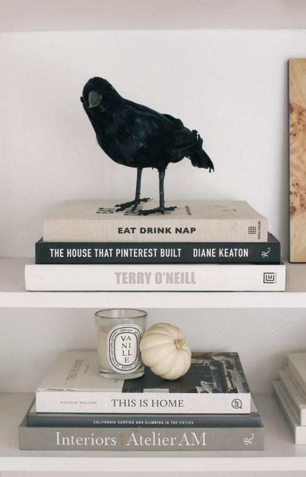 minimalistische Halloween Deko Bücher ein schwarzer Rabe darauf Symbol für Weisheit