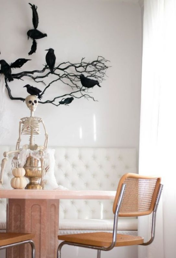 minimalistische Halloween Deko Essecke in hellen Farbtönen schwarze Zweige Raben an der Wand Skelett auf dem Tisch zwei kleine Kürbisse
