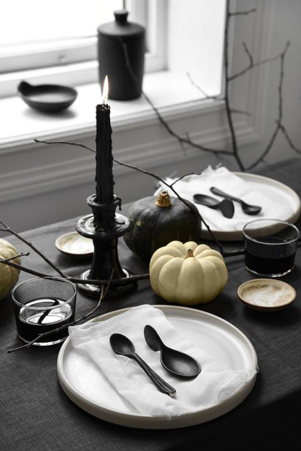 minimalistische Halloween Deko Esstisch am 31.Oktober schwarzes Geschirr Besteck schwarze Tischdecke kahle Zweige schwarze Kerze