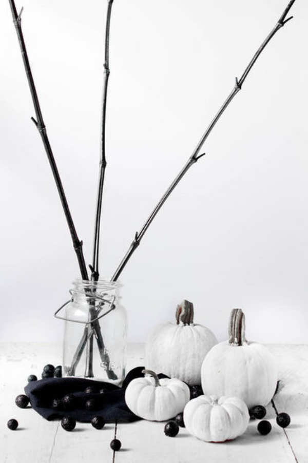 minimalistische Halloween Deko kleine weiße Kürbisse schwarze Bälle Glas kahle Zweige
